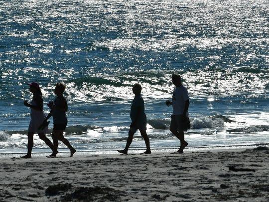 Beachgoers stroll along the beach in Indialantic. FILE.