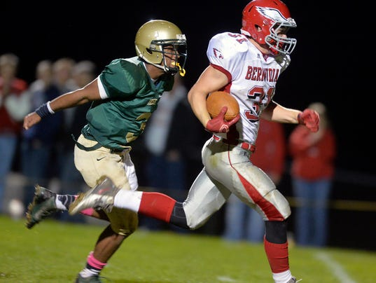 Bermudian Springs' Colton Dull outpaces York Catholic's Hakeem Kinard for a touchdown in the second half of a football game at York Catholic on Friday. Bermudian Springs defeated York Catholic 42-21. (Photo by Chris Dunn - Daily Record/Sunday News)