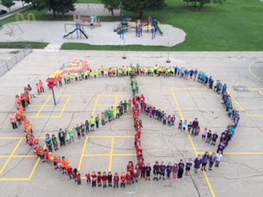 Roosevelt and Alliance students gathered on their playground recently to create a peace symbol to recognize the International Day of Peace.