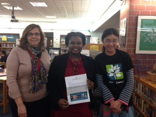 Maya Mau, right, a sixth-grader at Community Middle School in Plainsboro, was among the winners of the Kid's Corner 2014-2015 Winter Essay Contest sponsored by the Charles Lafitte Foundation. She is shown with English teacher Karen Black, left, and Principal Shauna Carter.