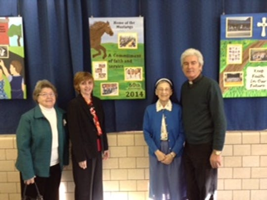 Geraldine Taormina, left, a former educator at St. Mary's Prep in Denville, Margaret McCluskey, current school principal, Sister Mary Joan, former principal, and Father Martin Glynn, pastor of St. Mary's Parish, stand in front of the artwork during an alumni breakfast held on Jan. 29.
