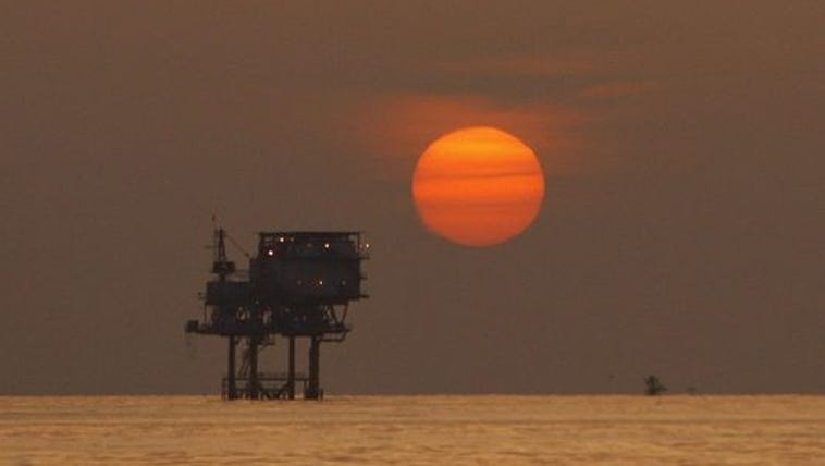 The sun sets over an oil well in the Gulf of Mexico