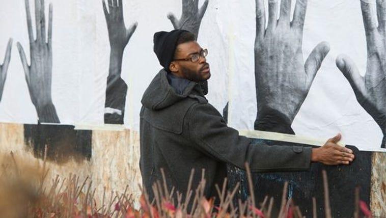 Lenard Blair helps hang the artwork of St. Louis artist