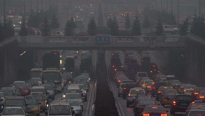 Vehicles crawl along a major road in Beijing in January, surrounded by thick smog.