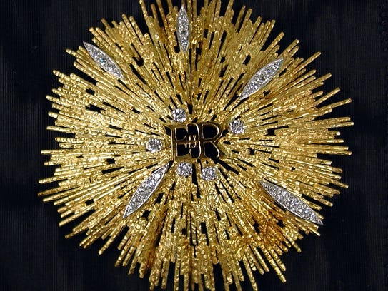 A gold starburst brooch studded with diamonds and featuring