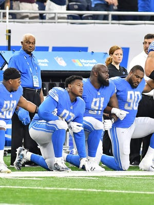 Some Lions players, including Akeem Spence (center), kneel and others stand, arm in arm, during the national anthem before a September game against the Altanta Falcons at Ford Field.