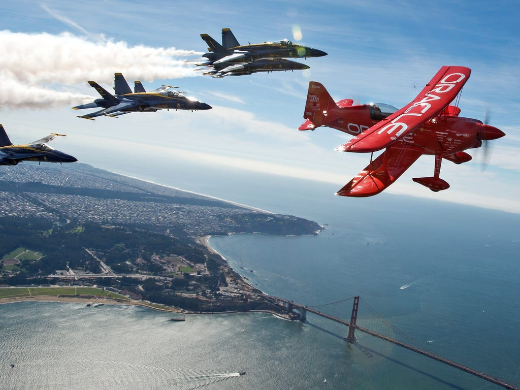 Team Oracle pilot Sean Tucker  flies ahead of the U.S. Navy Blue Angels as part of a practice run for Fleet Week over the bay in San Francisco.