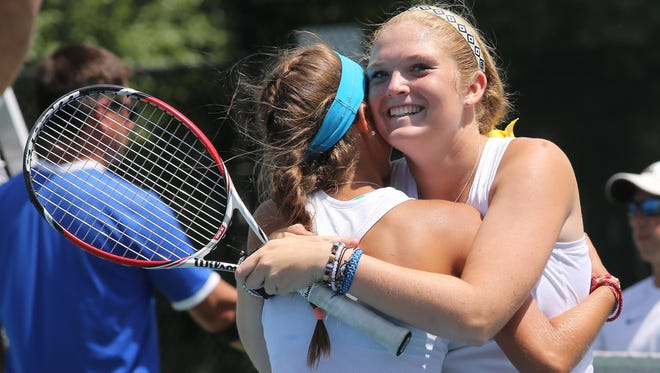 Emma Love, left and Molly Fletchall of Carmel hug after winning the match.