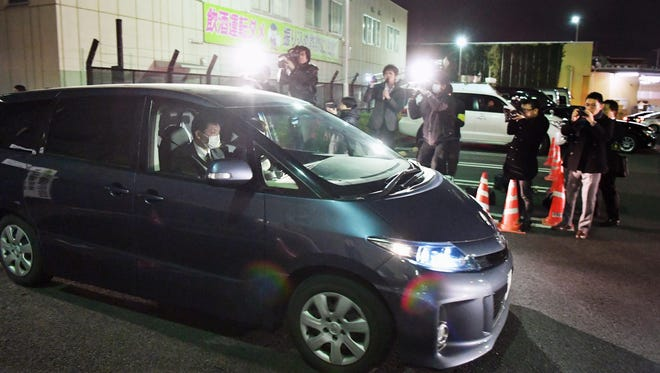 In this Sunday, March 27, 2016 photo, a police car carrying a girl who had been abducted, leaves the police headquarters in Niiza, Saitama prefecture, near Tokyo. Japanese police captured the 23-year-old man in an abduction case after a teenage girl escaped and ran for freedom a day earlier after being held captive in his apartment for nearly two years.