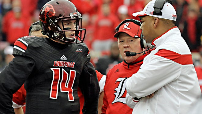 "The offensive ""brain trust"" of Louisville's football team, quarterback Kyle Bolin (13), head coach Bobby Petrino, center, and offensive coordinator Garrick McGee, right, discuss options during a timeout in their NCAA college football game Saturday, Nov. 29, 2014, in Louisville, Ky. (AP Photo/Garry Jones)"