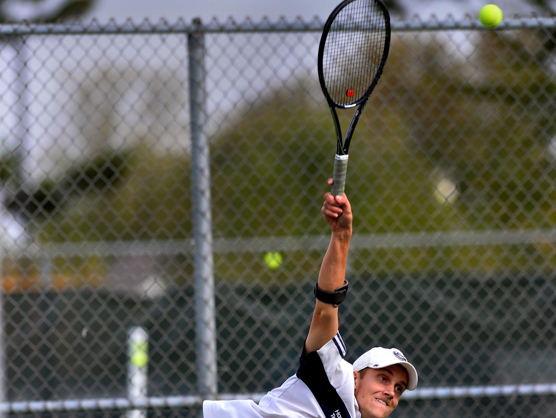 Haslett's Matthew Stewart serves Thursday 10/8/2015 in early action of tennis regionals.