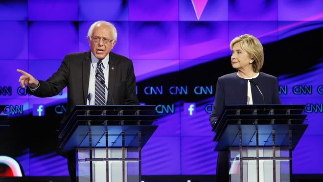 Hillary Clinton, right, listens as Sen. Bernie Sanders of Vermont speaks during the CNN Democratic presidential debate Oct. 13 in Las Vegas.