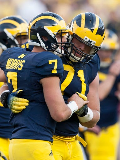 Michigan quarterback Shane Morris is helped off the field by offensive linesman Ben Braden after being tackled in the fourth quarter.