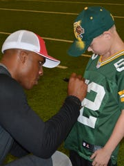 Jermichael Finley signs an autograph for a Packers