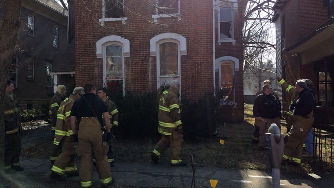 Chillicothe firefighters gather outside the scene of a fatal fire at 64 W. Fourth St. Sunday.