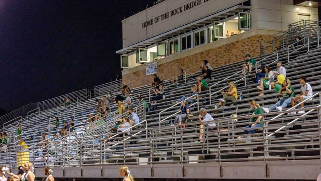 A limited number of socially distanced spectators look on from the stands during Rock Bridge's home football game last Friday night.