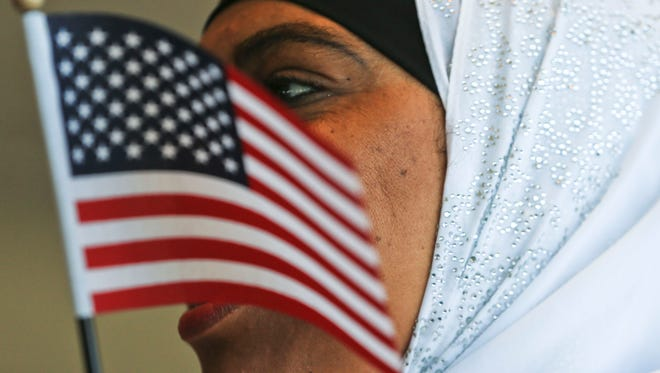 Zuiekha Khaleel holds a small American flag while waiting for the Naturalization ceremony U.S. citizen Friday at the Muhammad Ali Center near the Worldfest. More than 100 people became U.S. citizens during the ceremony.