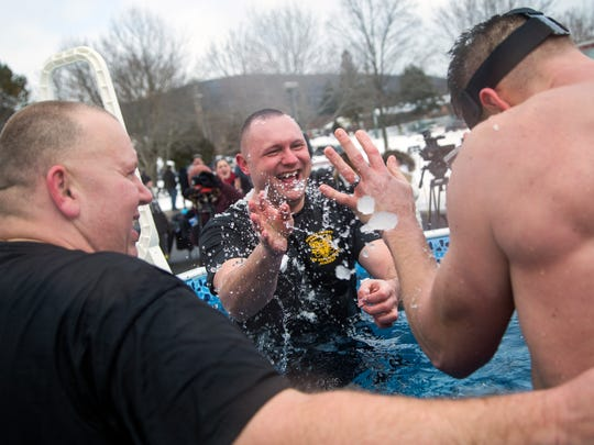 Broome County Sheriff's Office Lt. Ben Harting, center, throws ice at New York State University Police officer Luke Walton while taking a Polar Plunge at SUNY Broome Community College.