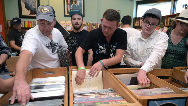 Record fans search the bins at Grimey's Too during Record Store Day on Saturday, April 16, 2016.