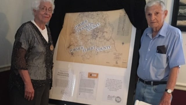 Joyce Hilliard accepts framed copy of the late 1700's map reconstructed by her late husband Sam, from and Dan Crumpton.
