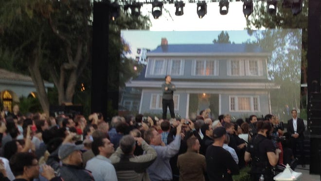 Elon Musk points out a solar roof on one of the movie set houses at Universal Studios Hollywood
