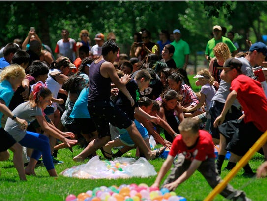 Participants race for water balloons on July 4, 2016,