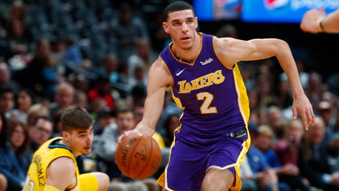 Los Angeles Lakers guard Lonzo Ball, front, drives past Denver Nuggets forward Juan Hernangomez, of Spain, as he falls to the floor in the first half of an NBA basketball game Saturday, Dec. 2, 2017, in Denver. (AP Photo/David Zalubowski)
