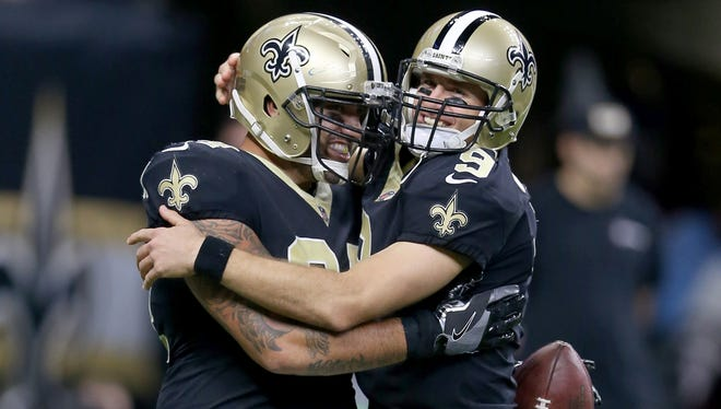 New Orleans Saints tight end Michael Hoomanawanui (84) is congratulated by quarterback Drew Brees (9) after his touchdown catch in the second half against the Detroit Lions at the Mercedes-Benz Superdome.