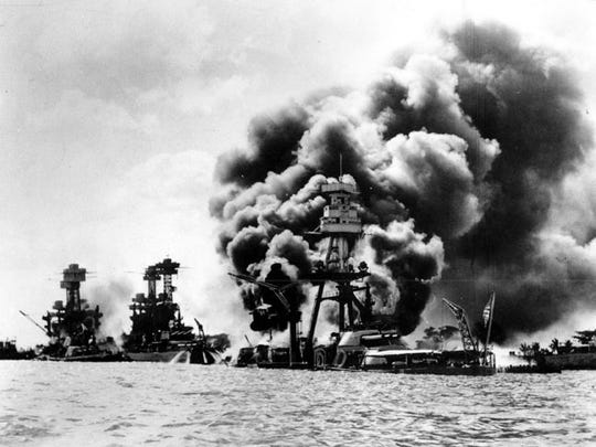 In this Dec. 7, 1941 file photo released by the U.S. Navy, three U.S. battleships are hit from the air during the Japanese attack on Pearl Harbor.  From left are: USS West Virginia, severely damaged; USS Tennessee, damaged; and USS Arizona, sunk.
