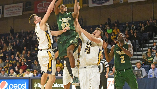 CSU's J.D. Paige goes up between Northern Colorado defenders Spencer Mathis, left, and Tanner Morgan while putting up a shot Sunday in the Rams' 73-64 loss to Northern Colorado in Greeley.