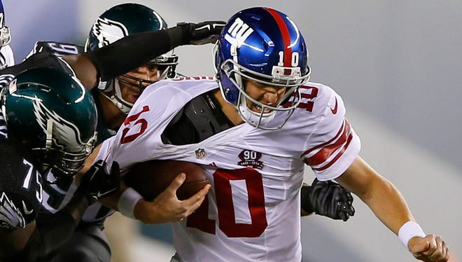 Giants quarterback Eli Manning, right, is hoping his offensive line handles itself better than it did against Philadelphia.