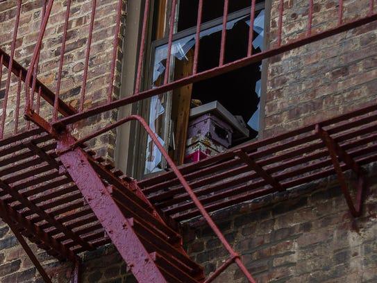 Boxes are seen through a broken window near a fire