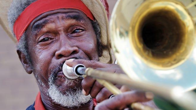 John Mills, aka John the Revelator, plays slide trombone to entertain and attract customers to Athena's in this Advertiser file photo.