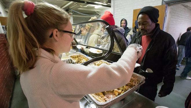 Lexi Russell, 17, Carmel, serves turkey to Robert McBride, during a Christmas dinner sponsored by SS. Peter and Paul Cathedral, and a group of Jewish volunteers from Beth-El Zedeck, Friday, Dec. 25, 2015.
