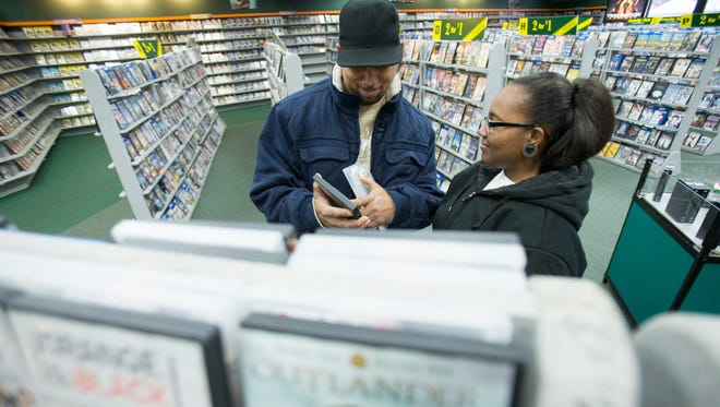 John Starks (left), with his daughter Teresa Gamill, look for a title at Family Video, located at the corner of Emerson and 10th, in Indianapolis, on Dec. 21, 2015.