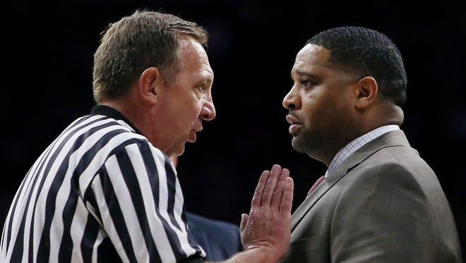 """Referee David Hall talks with Emanuel """"Book"""" Richardson, assistant coach, during a timeout in the second half in a game at McKale Center on Sunday January 29, 2017."""