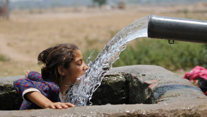 A girl drinks water from an irrigation tube on a hot