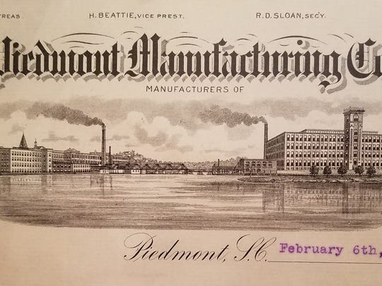 Letterhead of the Piedmont Manufacturing Co. The image shows mills operating on either side of the Saluda River, which the footbridge in between.
