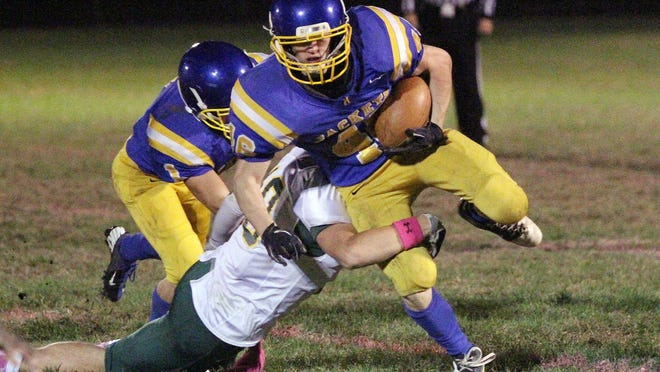 Milton's Brad Bombard is tackled by Burr and Burton's Ryan Smith in the first half of a 2014 high school football game.