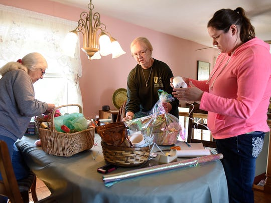 """Mary White-Levilain, left, Jerilyn Petersen, center, and Jackie Crever assemble baskets for the upcoming Central Minnesota Women Shine """"Spring Into Windows"""" fundraiser March 31 at the Red Carpet Martini Lounge in St. Cloud."""