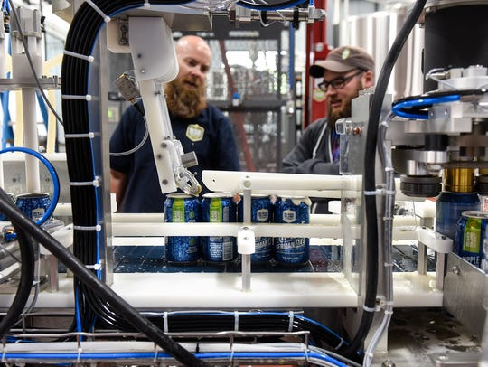Cans are filled with beer on the canning line Wednesday,