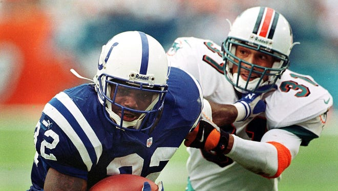 Indianapolis Colts running back Edgerrin James (L) runs the ball around the defense of Miami Dolphins safety Brock Marrion during second quarter action of their game 05 December 1999 at Pro Player Stadium in Miami, Florida. The Colts defeated the Dolphins 37-34.