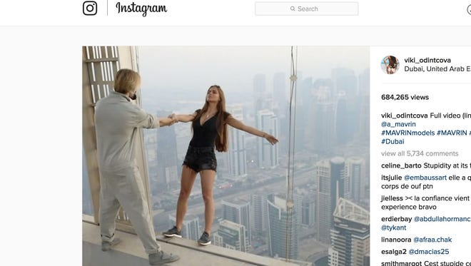 A video taken of the incident shows Viki Odintcova, 23, lean off the ledge of a skyscraper as a male assistant holds her hand, and later dangling off of the 1,004-foot-high Cayan Tower.