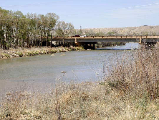The San Juan River flows under a bridge Friday along the Among the Waters river trail in Farmington.