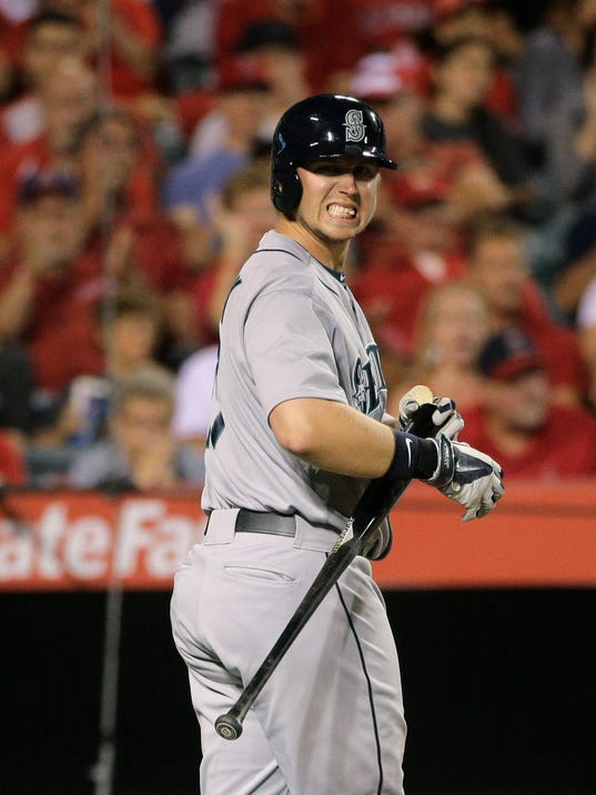 Seattle Mariners' Justin Smoak reacts after swinging on a pitch during the sixth inning of a baseball game against the Los Angeles Angels on Friday, July 18, 2014, in Anaheim, Calif. Smoak struck out on the at-bat. (AP Photo/Jae C. Hong)