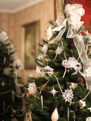 """The parlor tree decorated by the Earth, Wind and Flowers Garden Club reflects in the long mirror of the Bucyrus Historical Society. A """"White Christmas"""" reigns inside and out."""