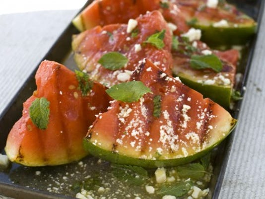 Grill watermelon and mix it with spinach. It's a healthier side compared to the usual potato or pasta salad. (Associated Press -Matthew Mead)