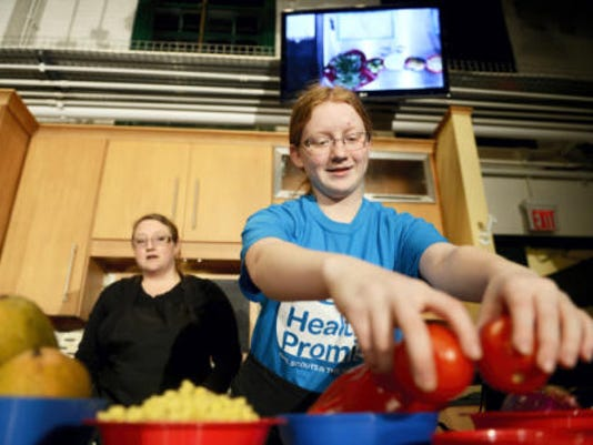 Collandra Runkle, 14, of West York, preps ingredients while Brandy Boswell of West York, co-leader for Teen Battle Chef, looks on at YorKitchen in York Wednesday. Runkle and a fellow senior chef hosted a livestreamed healthy cooking video chat for Girl Scouts of the Heart of Pennsylvania. This was the third of four video chats in four months featuring local teen chefs from Spoutwood Farm to teach Girl Scout participants about healthy cooking. (Kate Penn -- Daily Record/Sunday News)