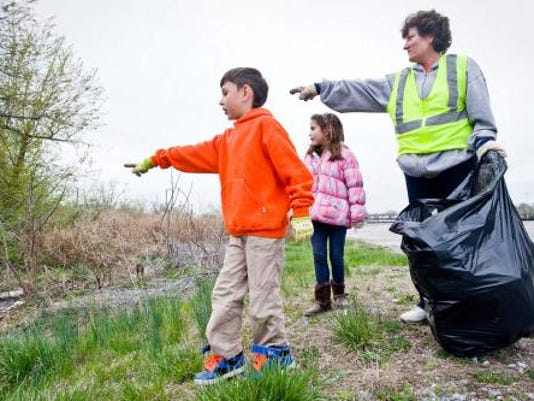 Mateo Maldonado, 7, left, Nataleah Abate, 6, and Lynn Rodenhaber spot a new pile of trash to pick up along Loucks Mill Road in Spring Garden Township on April 15, 2013. Maldonado's group of 'Litter Critters' has been cleaning up areas in and around the city for months. He is preparing an even larger cleanup project for Earth Day. (FOR THE DAILY RECORD/SUNDAY NEWS -- JEFF LAUTENBERGER)