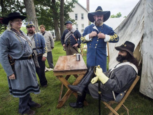 """Jeff Cheeks, of Gettysburg, center right, buttons his coat as he portrays Gen. Richard S. Ewell of the 2nd Corps on June 28, 2015. Cheeks and the other re-enactors with him are members of the American Living History Education Society. In reference to the Confederate flag controversy, Cheeks said helping visitors learn about history was his priority. """"We're here to represent history. To honor those guys is more important than flying that flag."""""""
